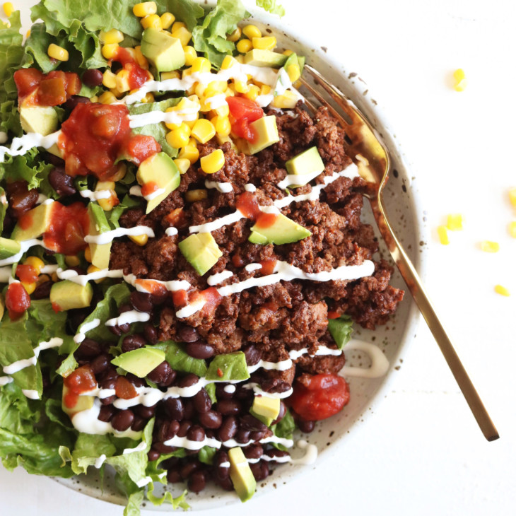 This is an overhead image of a bowl filled with lettuce, ground beef, salsa, avocado, corn, black beans, and sour cream. The bowl sits on a white counter and a gold fork lies partially in the bowl.