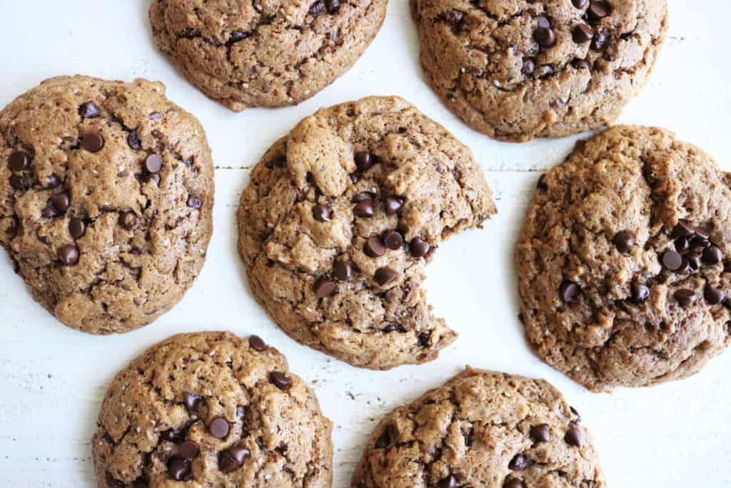 This is an overhead image of almond butter cookies with chia seeds and mini chocolate chips. The cookies sit on a white surface and the middle cookie has a bite taken out of it.
