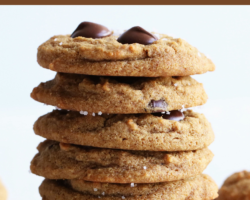 "This is a stack of chocolate chip cookies on a white surface. More cookies are blurred in the background. Text overlay reads ""tigernut flour cookies"""