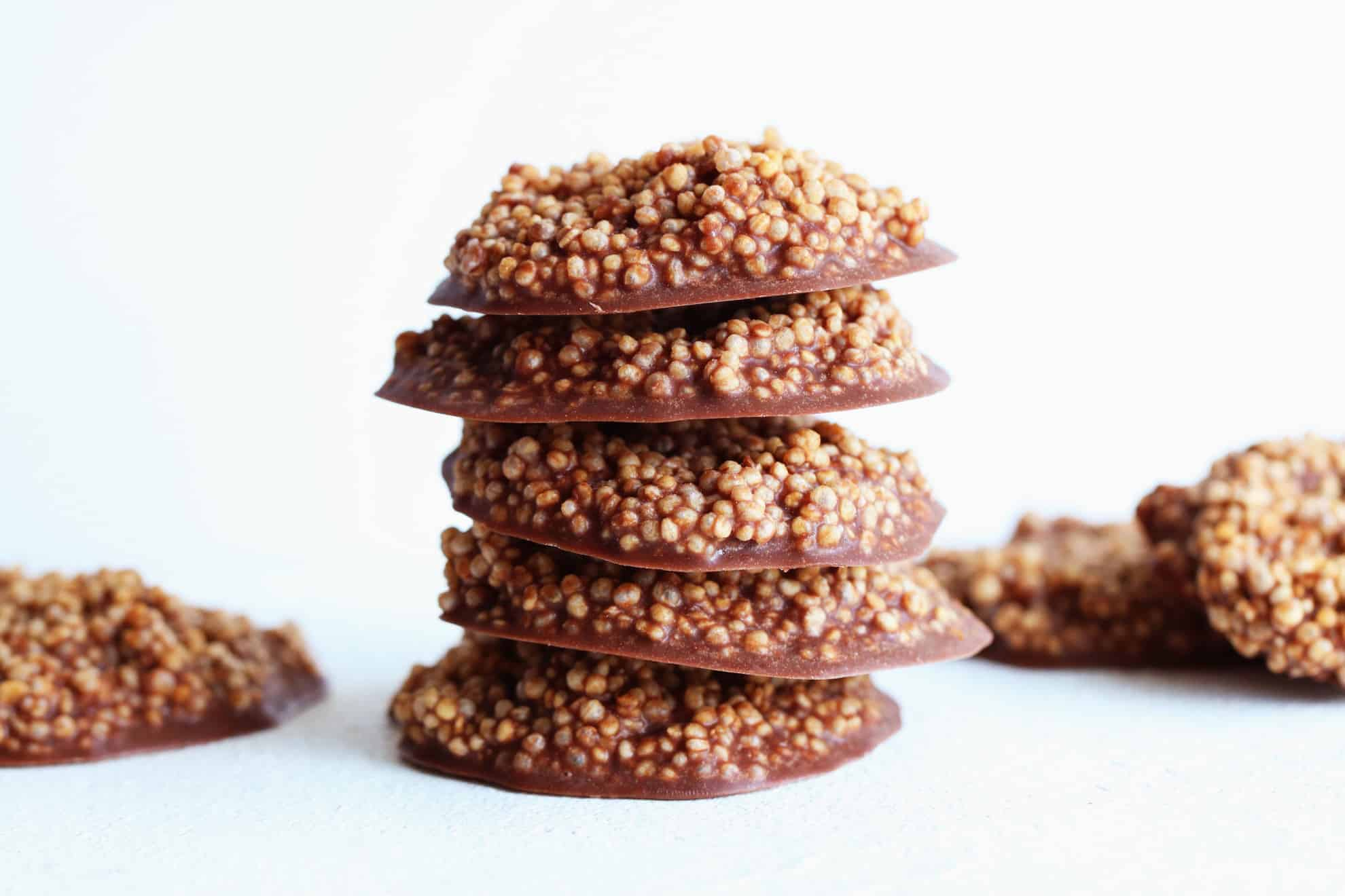 stack of Chocolate Quinoa Crisps on white counter and white background
