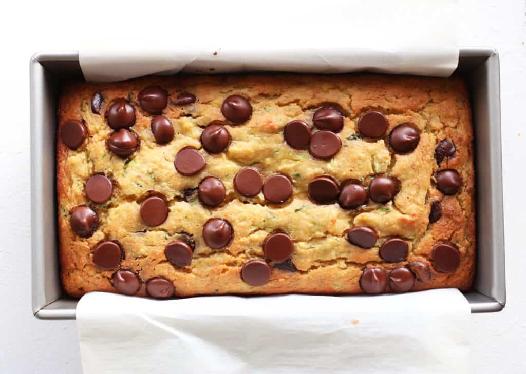 This is an overhead image of zucchini bread in a loaf pan with white parchment paper. The bread is topped with chocolate chips.
