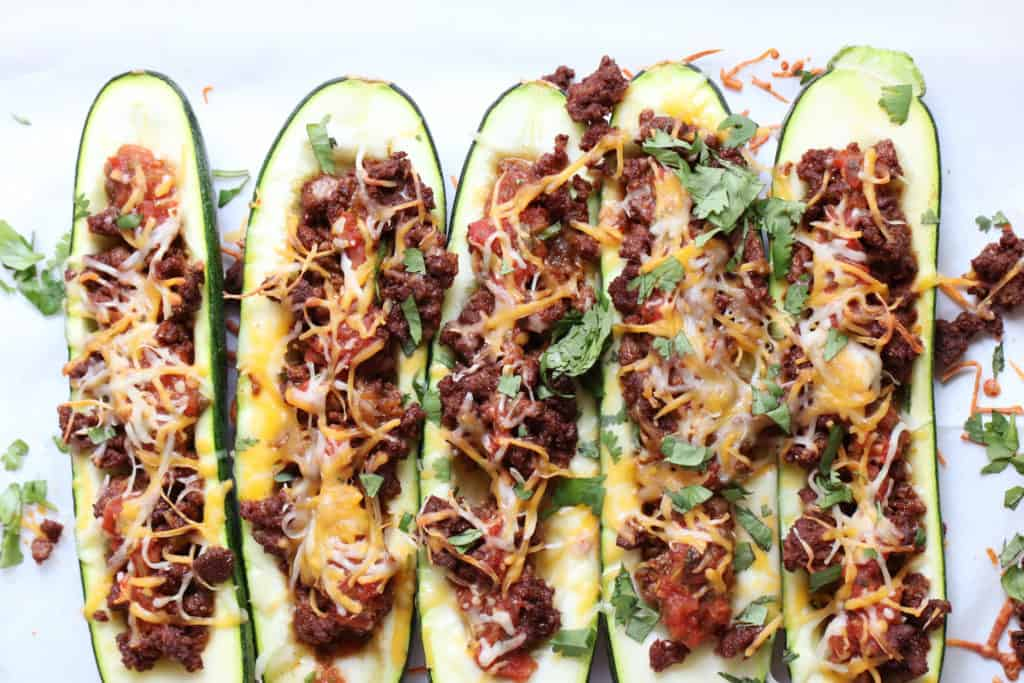 This is an overhead image of healthy taco zucchini boats topped with cheese, fresh cilantro and meat.