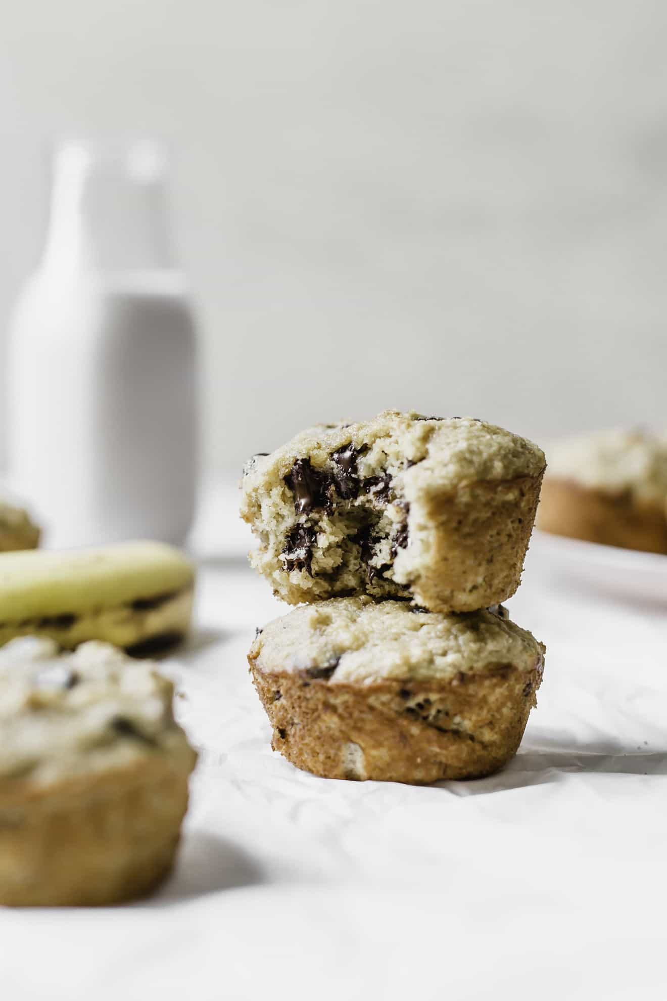 This is a side view of two banana muffins stacked on top of each other. The top muffin has a bite taken out revealing melty chocolate chips. The muffins sit on a white surface with a banana, more muffins, and a jug of milk blurred in the background.