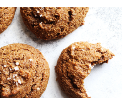 "overhead image of a ginger molasses cookie on a white counter with a bite taken out, text overlay ""ginger molasses cookies gluten free & dairy free"""