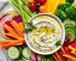 This is an overhead image of a white bowl filled with a creamy dip. The dip is topped with a drizzle of olive oil and fresh herbs. Around the dip are fresh veggies like cut peppers, radish, carrots, cucumbers, and celery.