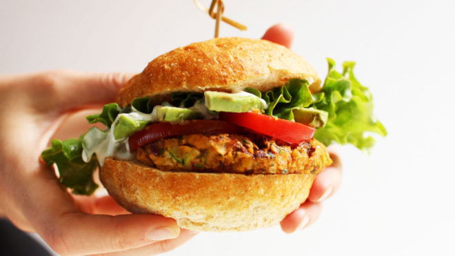 Two hands hold a vegetable zucchini chickpea burger in a bun. Lettuce, avocado, and tomato is on top of the burger.