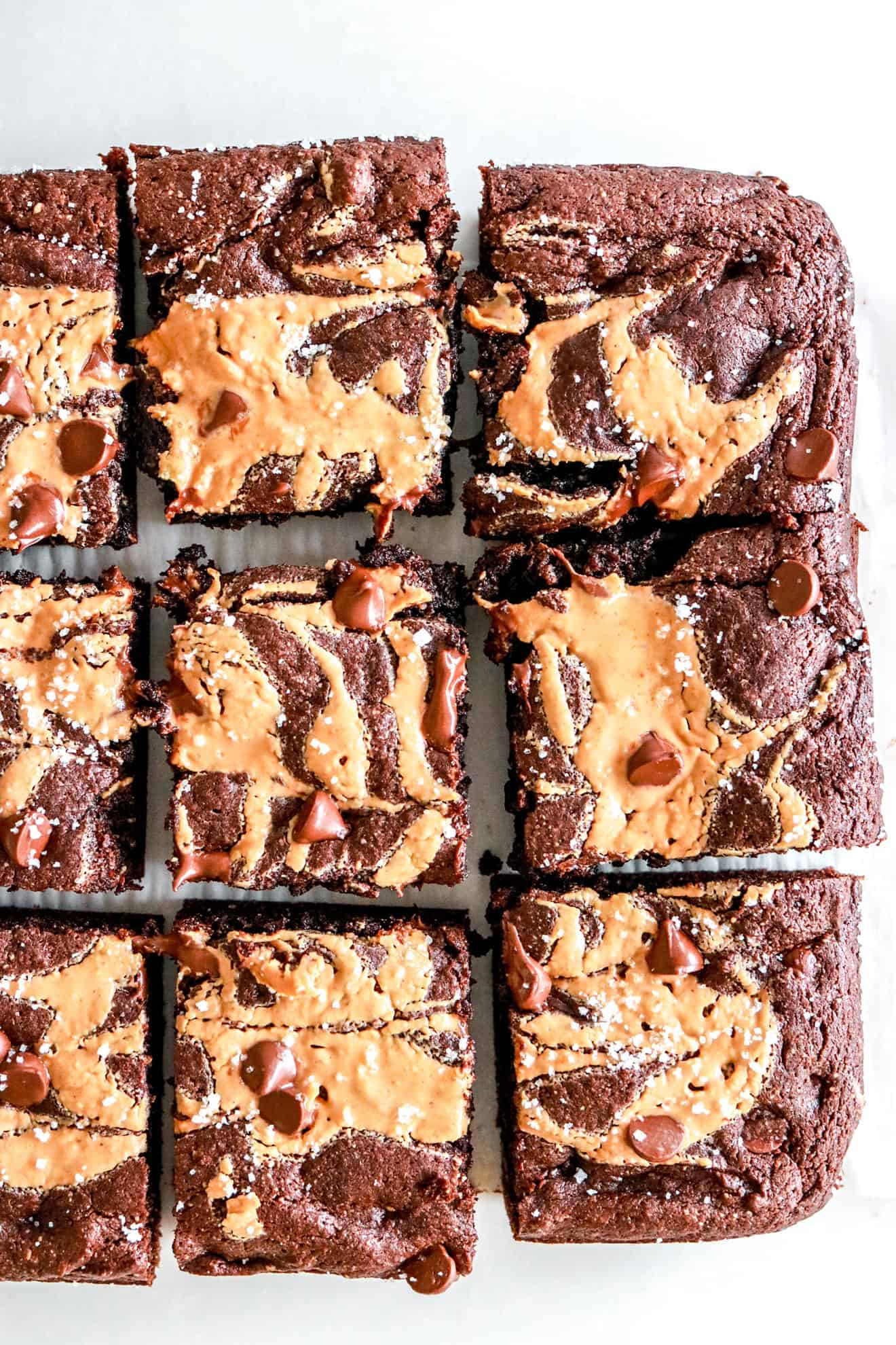 chocolate brownies with a peanut butter swirl, melty chocolate chips and sea salt on a white background