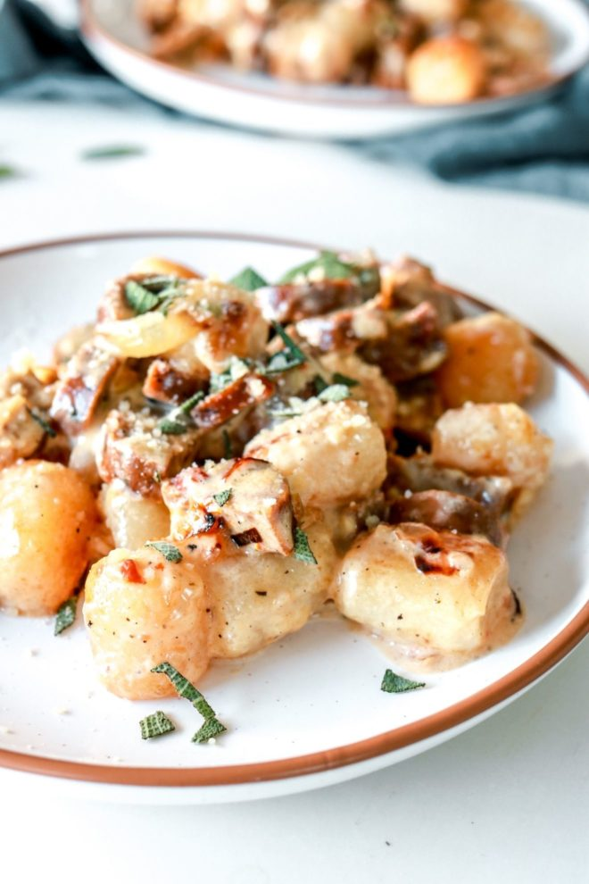 side image of cauliflower gnocchi in a creamy Parmesan sauce with caramelized onions, sausage, and chopped sage