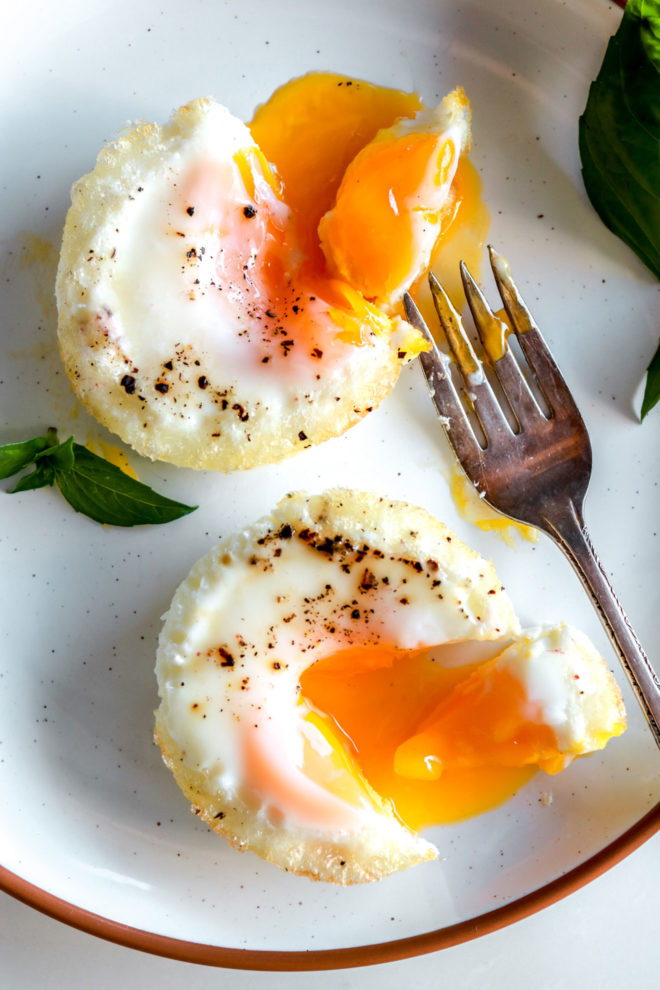 plate with two oven-baked eggs with drippy yolks and a fork