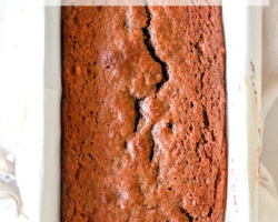 """overhead image of a loaf pan with parchment paper and a baked gingerbread load text overlay """"gluten free & dairy free gingerbread banana bread"""""""