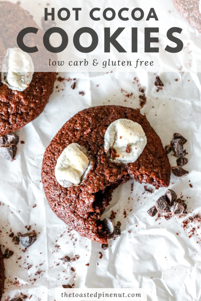 "overhead image of a chocolate cookie with marshmallows and a bite taken out. The cookie sits on white parchment paper with chopped chocolate sprinkled around it. text overlay ""hot cocoa cookies low carb & gluten free"""