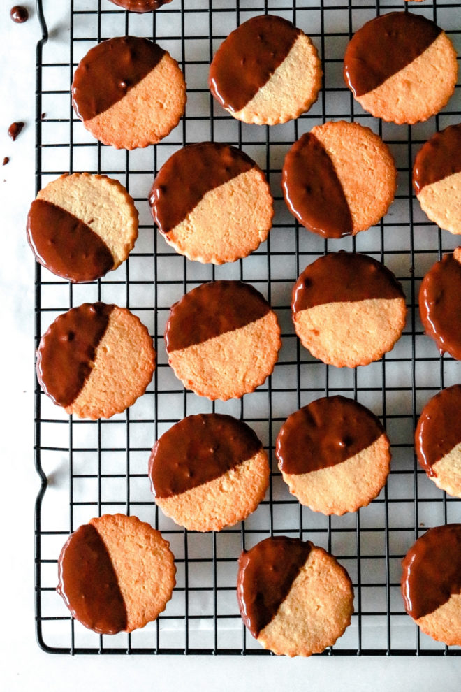 overhead image of a black cooling rack with circle shortbread cookies half dipped in chocolate
