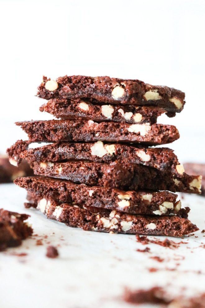 This image is a side view of a stack of brownie brittle with nuts in it. The stack sits on a white counter with other brownie brittle pieces blurred in the background.