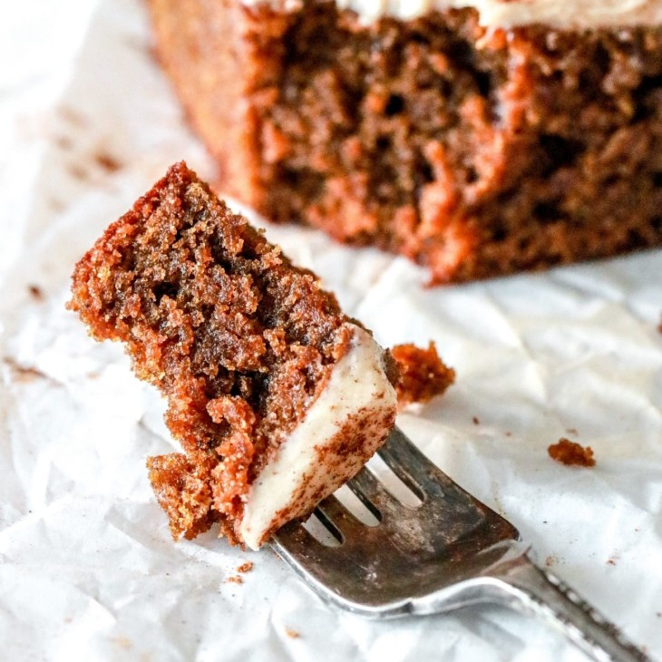 a fork with a bite of gingerbread cake with vanilla icing lays on a white piece of parchment paper. the rest of the slice of cake is blurred in the background.