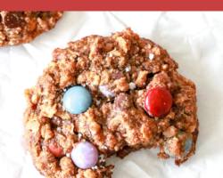 "This is an overhead image of a monster cookie with M&Ms and oats with a bite taken out. The cookie lays on a piece of parchment paper. Text overlay reads ""gluten free healthy monster cookies."""