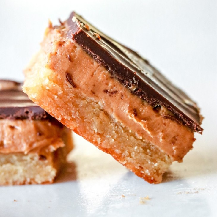 side view of a peanut butter millionaire bar leaning against another bar. both bars sit on a white counter and have three layers: a shortbread layer, peanut butter layer, and chocolate layer.