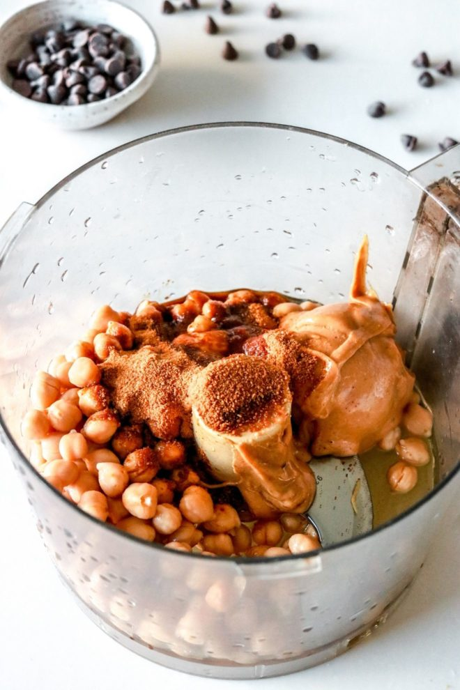 This is an overhead image looking down into a food processor with chickpeas, peanut butter, and sugar inside. Chocolate chips are in a small bowl blurred in the background.