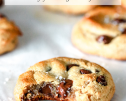 """This is a side view of a chocolate chip cookie with a bite taken out of it. The Cookie sits on a white piece of parchment paper with more cookies blurred in the background. Text overlay reads """"chocolate chip tahini cookies dairy free & gluten free."""""""