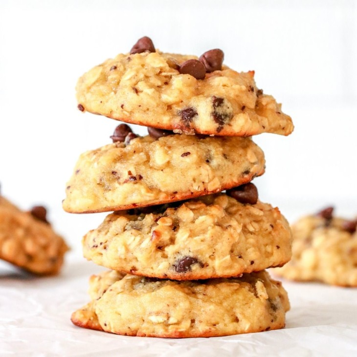 This is a side view of a stack of four oatmeal chocolate chip cookies sitting on a white counter. More cookies are blurred in the background.