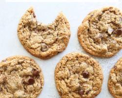 """This is an overhead image of chocolate chip cookies laid out on a white surface. One cookie has a bite taken out. Text overlay reads """"chewy chocolate chip cookies made with almond flour!"""""""