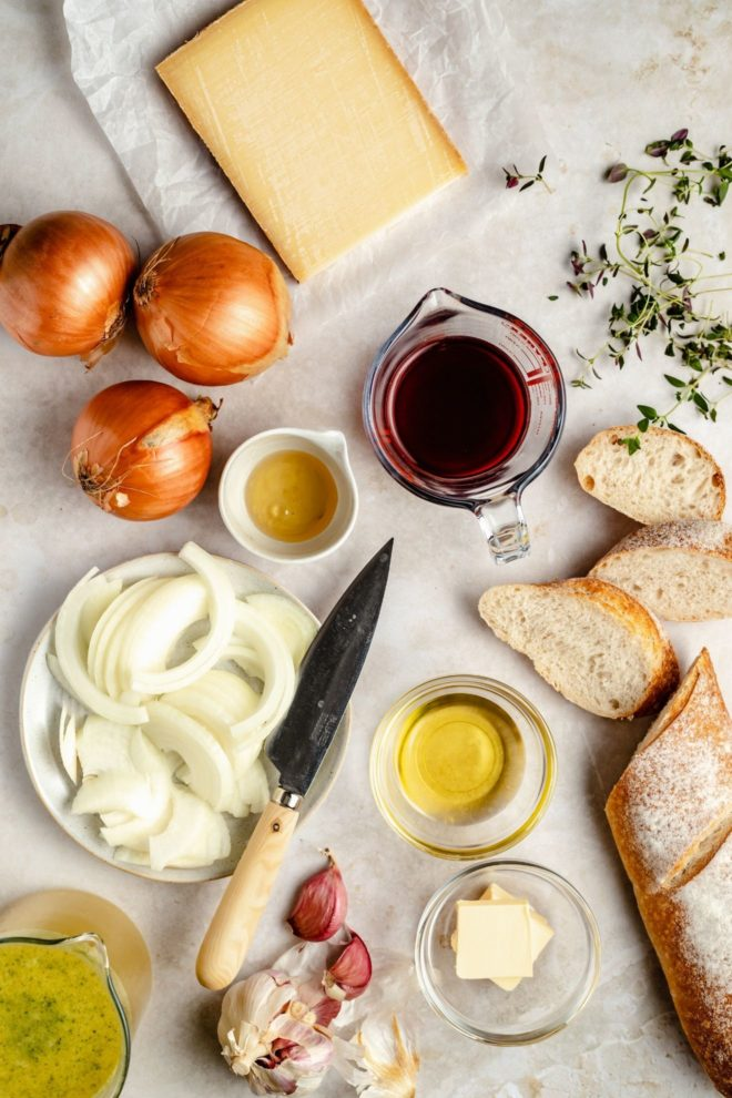 This is an overhead image of ingredients laid out on a white counter. The ingredients are cheese, onions, red wine, oil, butter, thyme, garlic, bread, and broth.
