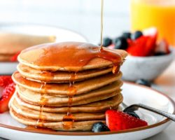 This is a side view of a stack of pancakes on a plate with berries. Syrup is being poured on top of the pancakes. More berries, pancakes, and orange juice is blurred in the background.