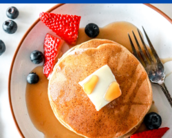 "This is an overhead image of pancakes on a plate with strawberries and blueberries. The pancakes have a pad of butter and syrup on them. Text overlay reads ""healthy oat flour pancakes"""