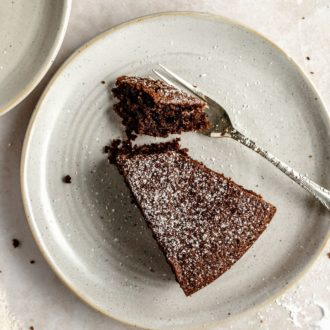 This is an overhead image of a small plate with a slice of chocolate olive oil cake. A fork is cutting off a bite of cake. The chocolate cake is sprinkled with powdered sugar.