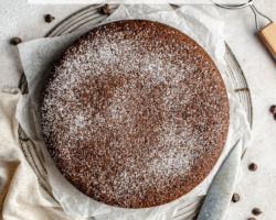 "This is an overhead image of chocolate olive oil cake. The cake sits on a piece of white parchment paper on a cooling rack. The cake is sprinkled with powdered sugar. A knife, chocolate chips, a tan tea towel, a sifter with powdered sugar, and small plated with forks on top are on the counter around the cake. Text overlay reads ""chocolate olive oil cake."""
