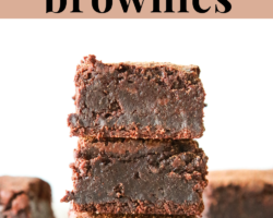 "This is a stack of three fudgey brownies. The brownies sit on a white piece of parchment paper and a white background. More brownies are blurred in the background. Text overlay reads ""intensely fudgey oat flour brownies."""