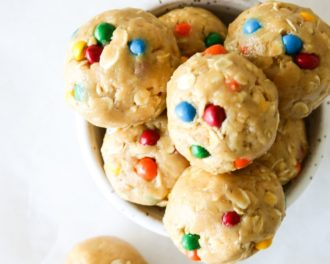 This is an overhead image of a small bowl filled with peanut butter and oat energy balls with rainbow candies pressed into them. The bowl sits on a white counter with more energy balls sitting on the counter around the bowl.