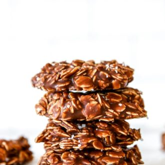 This is a side view of a stack of four chocolate oatmeal cookies. The cookies sit on a white counter with a white background with more cookies blurred in the background.