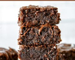 """This is a stack of four zucchini brownies with melted chocolate drizzling down the side. The stack sits on a white piece of parchment paper and a white background with more brownies blurred behind the stack. Text overlay reads """"the best zucchini brownies."""""""