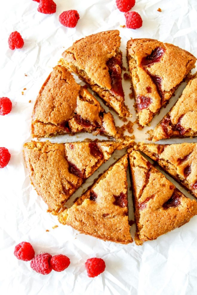 This is an overhead image of a lemon cake with raspberry jam swirl on top. The cake is cut into 8 triangles. The cake sits on a white surface with fresh raspberries on the side.