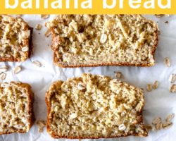 """This is an overhead image of slices of banana bread with oats sprinkled on top. The slices sit on a white piece of parchment paper with oats scattered around the banana bread slices. Text overlay reads """"7 ingredient oat flour banana bread."""""""
