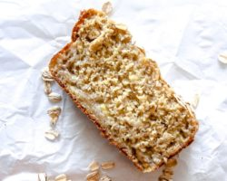 """This is an overhead image of a slice of banana bread on a white piece of parchment paper. There are oats sprinkled around the bread. The full loaf is blurred at the bottom of this image. Text overlay reads """"7 ingredient oat flour banana bread."""""""