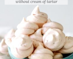 """This is a side view of a small green bowl sitting on a white surface with a white background. The bowl is filled with small strawberry meringue cookies and more cookies are on the white surface around the bowl. Text overlay reads """"strawberry meringue cookies without cream of tartar."""""""