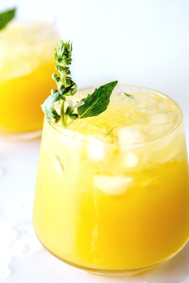 This is a side view of a glass on a white counter with water and ice around it. The glass has a yellow drink with crushed ice and another glass is blurred in the background. The drink is garnished with a basil flower and basil leaves.