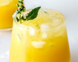 """This is a side view of a glass on a white counter with water and ice around it. The glass has a yellow drink with crushed ice and another glass is blurred in the background. The drink is garnished with a basil flower and basil leaves. Text overlay reads """"pineapple basil rum cocktails."""""""