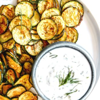 This is an overhead image of roasted zucchini discs on a white plate. The zucchini is served next to a small bowl of yogurt sauce.