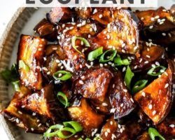 """This is an overhead image of a plate with caramelized, glazed eggplant pieces. The eggplant has sesame seeds and scallions on it. The plate sits on a white counter. Text overlay reads """"sweet & sticky air fryer eggplant."""""""