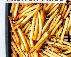 """This is an overhead image of an air fryer tray with cooked french fries on it. The fries are sprinkled with salt. The tray is on a white paper towel and on a white counter. Text overlay reads """"air fryer frozen french fries."""""""
