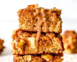 """This is a stack of three apple blondies sitting on a white counter. A cinnamon icing is drizzling down the side of the stack. More apple blondies are blurred in the background. Text overlay reads """"soft baked apple blondies."""""""