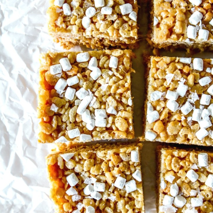 This is an overhead image of peanut butter rice krispie treats cut into squares and topped with mini marshmallows. The treats sit on a white piece of crumpled parchment paper.